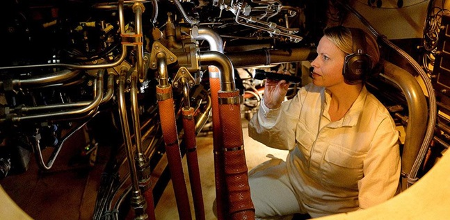 Female Marine Engineer Officer checking machinery with a torch