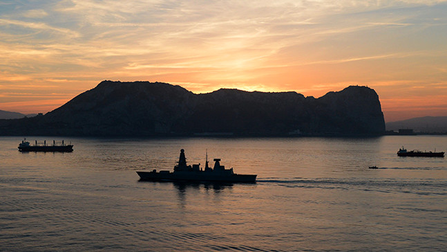 A Royal Navy ship in shadow against a sunset.