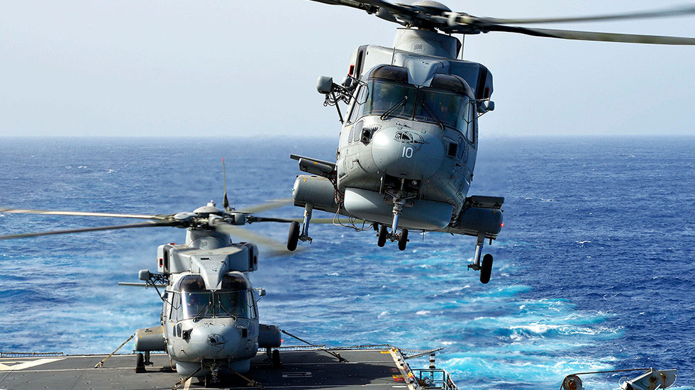 Two Royal Navy helicopters landing on a flight deck at sea.