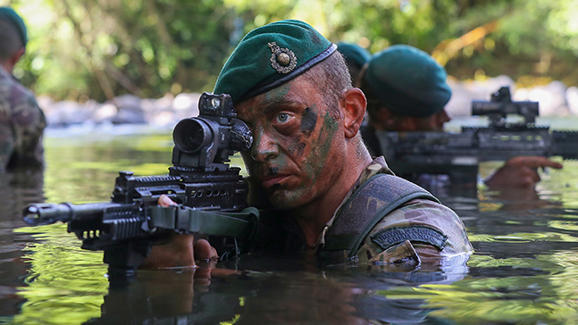 Royal Marines Commando in water pointing a gun