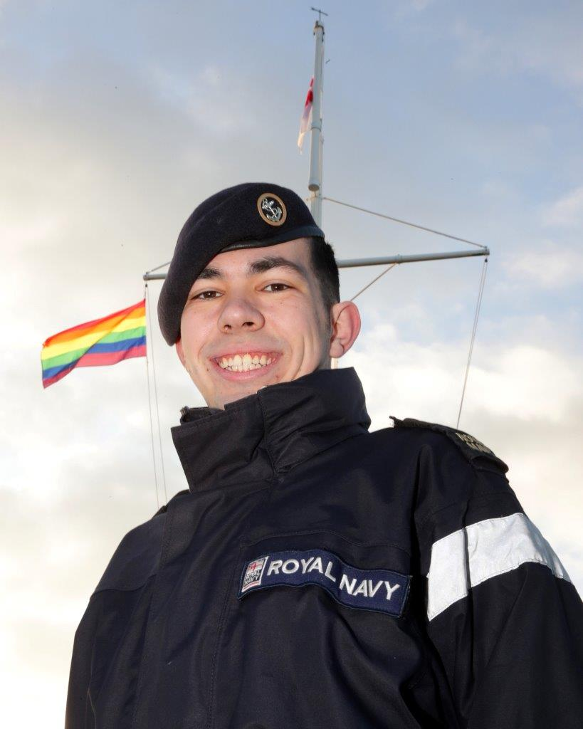 AET Thomas Smythe in front of the rainbow flag raised at RNAS Yeovilton