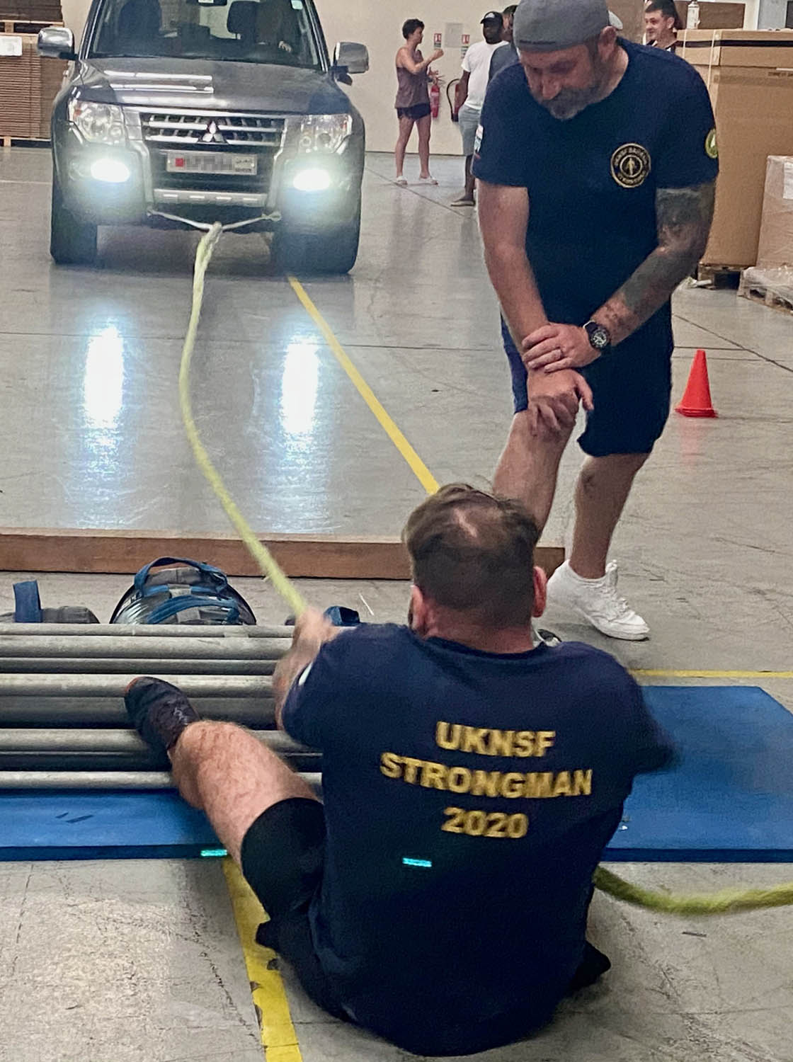A Royal Navy sailor pulls car in strongest man compeition