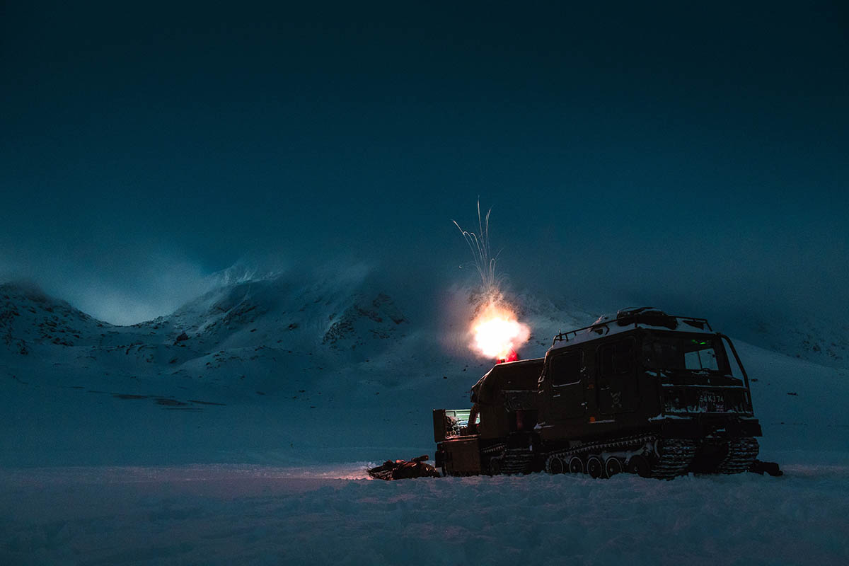 The flash of a mortar round leaving the barrel off the back of a mortar variant BV206 in front of a Norwegian mountain range at night.