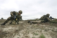 A Royal Marine moves positon as he gets protected by others on the section attack training