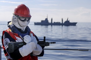 One of HMS Albion's sailors stands guard as the tanker ESPS Patino sails past