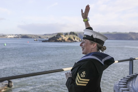 A female Leading Hand waves as HMS Albion enters Plymouth after 3 months away