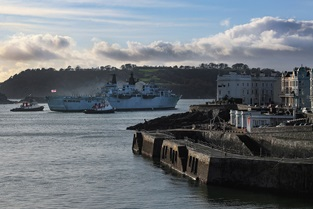 Shepherded by two tugs HMS Albion passes Plymouth's Grand Parade