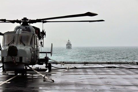 A Wildcat helicopter of 815 Naval Air Squadron lashed down on the deck of destroyer HMS Defender in the Channel, August 14 2019. Following Diamond is Indian guided-missile frigate Tarkash, also taking part in Exercise Konkan.