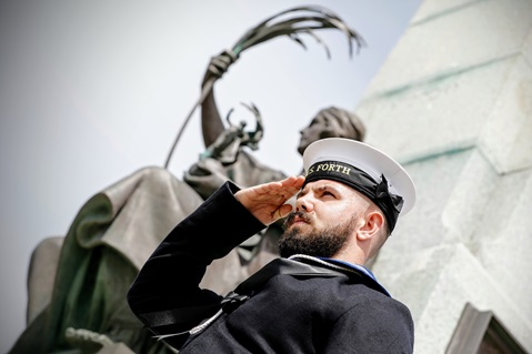 A sailor from HMS Forth salutes beneath the impressive Battle of the Falklands Memorial