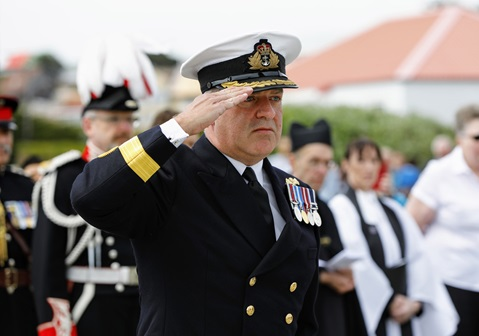 Commodore Jonathan Lett salutes after placing a wreath on the Falklands Memorial