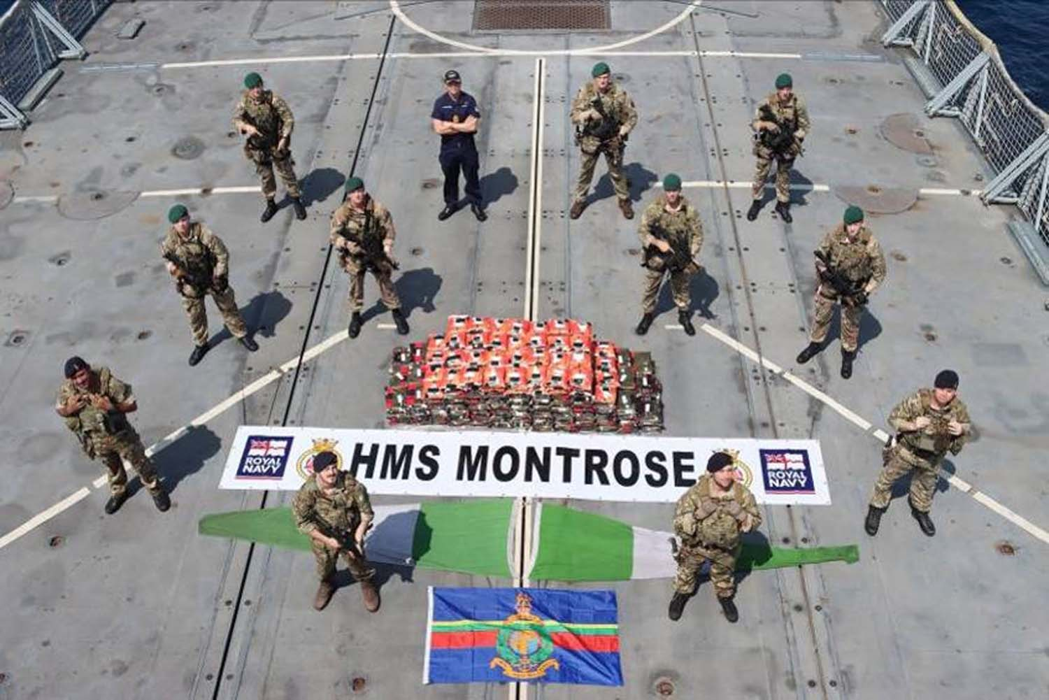 The boarding team from HMS Montrose, standing with the 450KG of methamphetamine seized during an operation in the Gulf