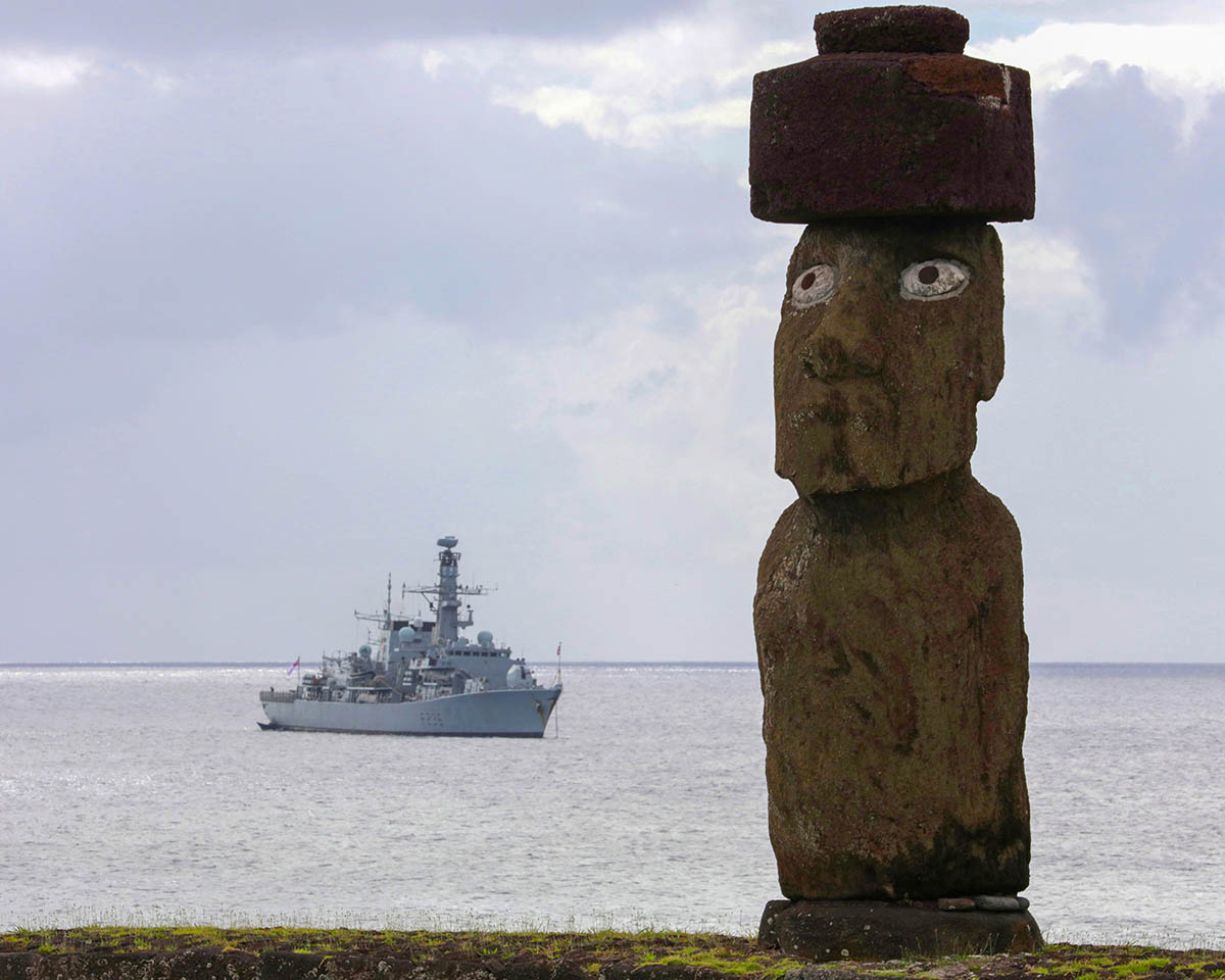A Lone Moi statue on Easter Island with HMS Montrose behind.