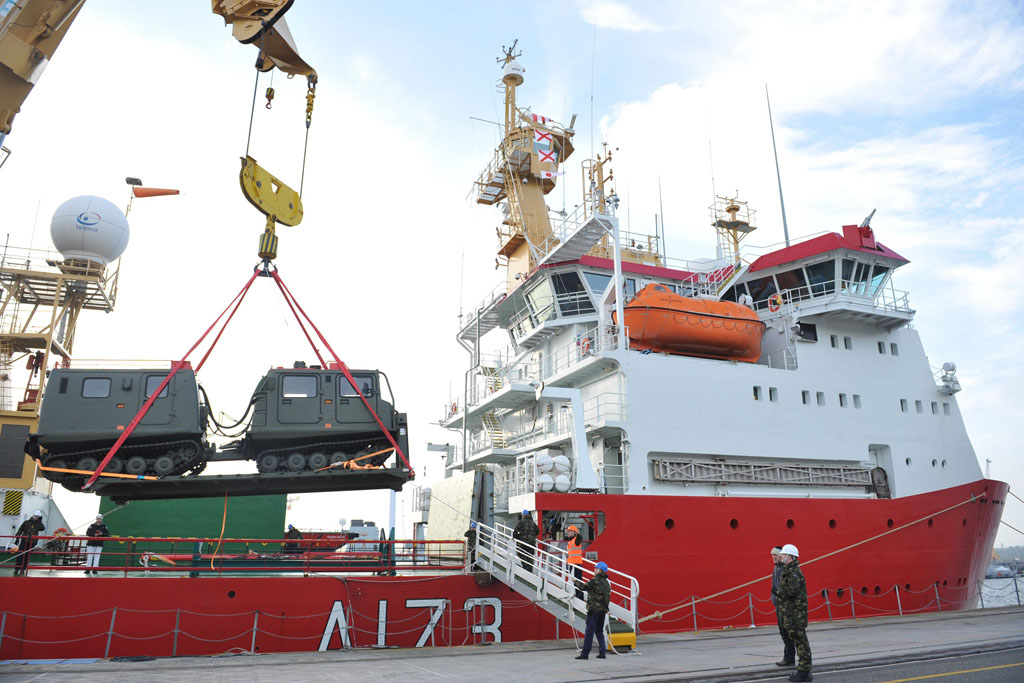 A BV all-terrain vehicle is craned onto the jetty from HMS Protector