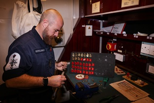 PO Andy Kirkaldy at work turning shell casings into poppies for shipmates