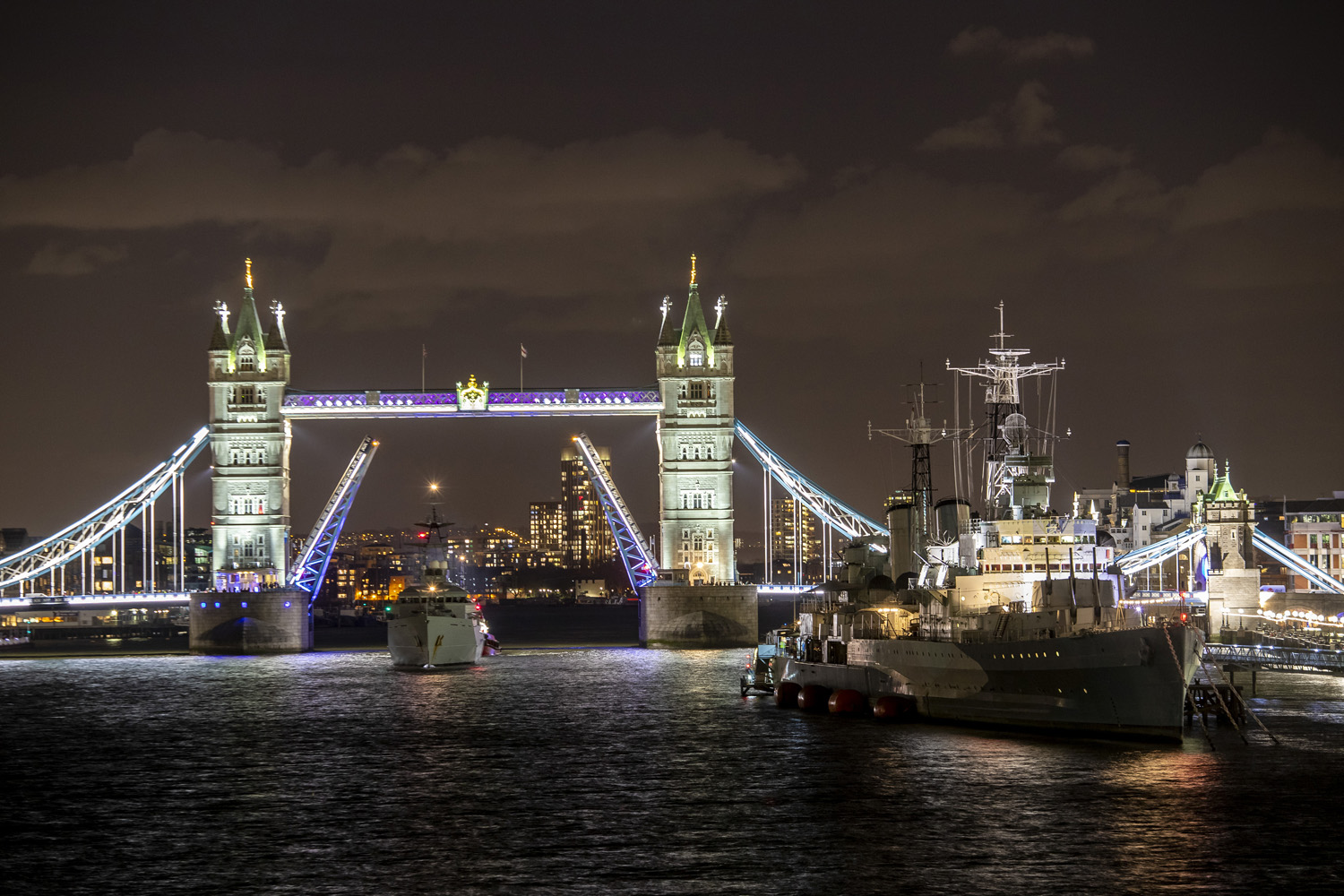 HMS Tyne sailing under the iconic Tower Bridge in London to moor alongside the equally iconic WWII Cruiser HMS Belfast.