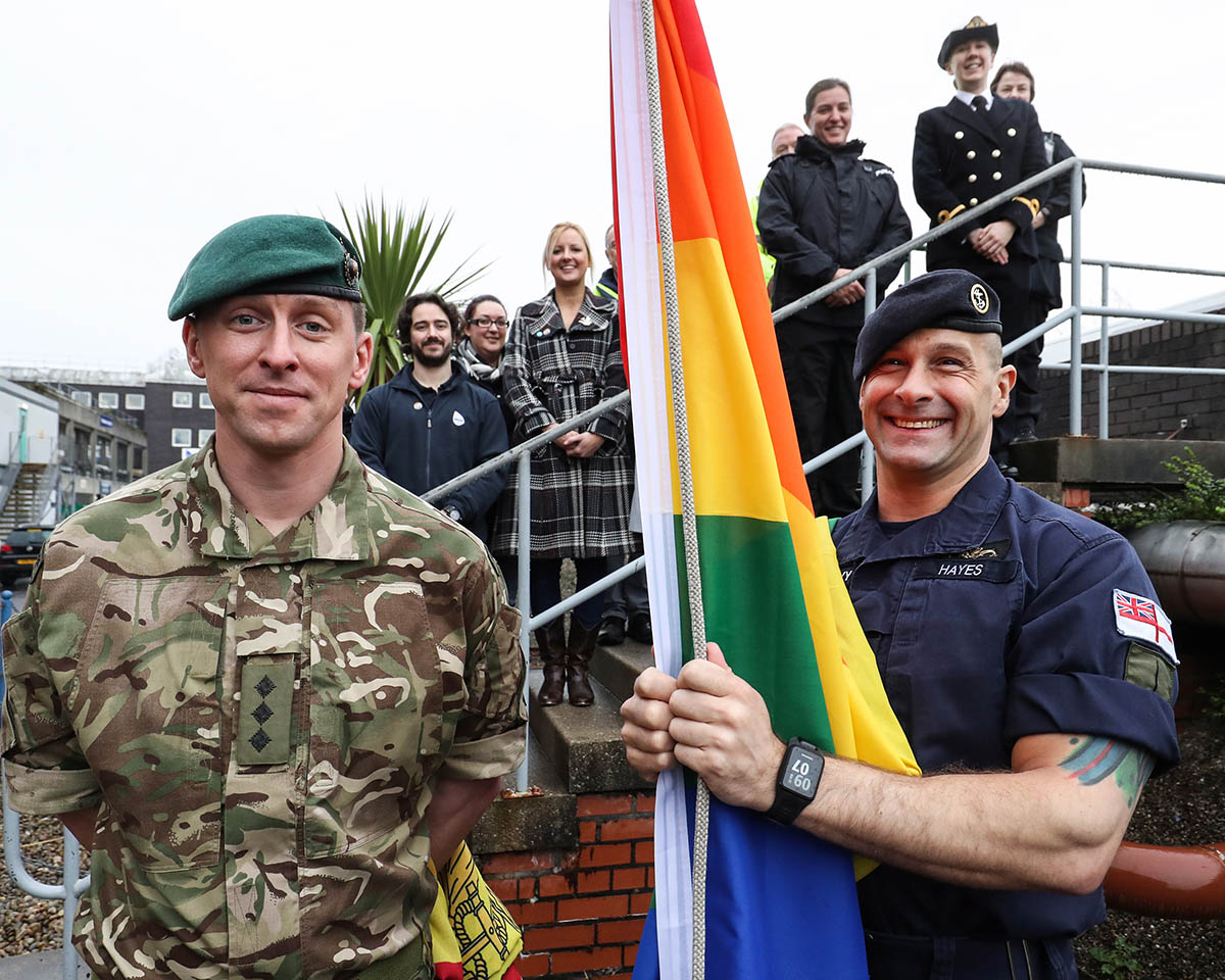 Rainbow flag with serving members of Royal Navy and Royal Marines personnel at HM Naval Base Clyde