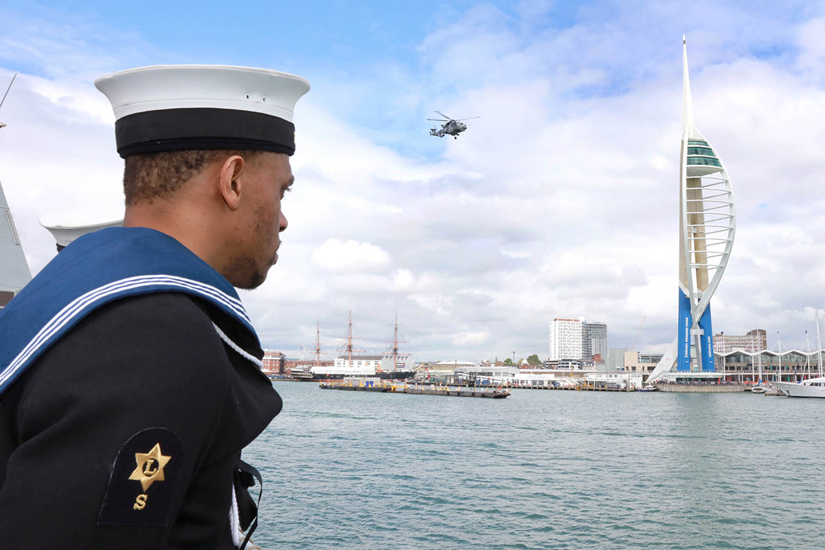 A sailor stands to attention as HMS Daring sails home and the ship's helicopter flies past Spinnaker Tower