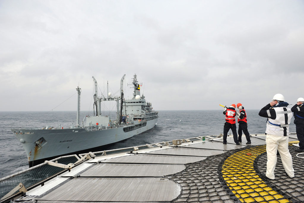 HMS Protector's gunline crew pass lines to RFA Black Rover